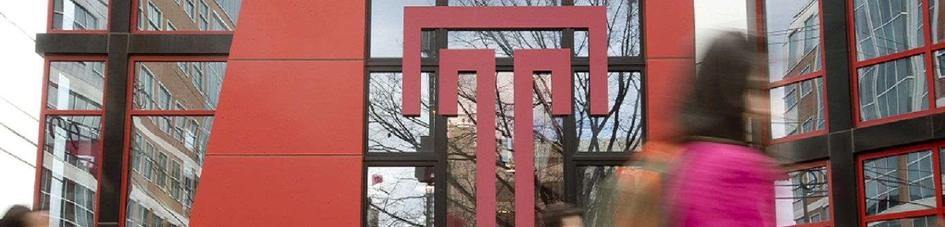 Students walking past the Temple T on the exterior of the Student Center